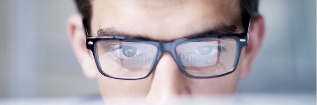 close-up photo of a man wearing eyeglasses who is very interesed in whatever he is looking at